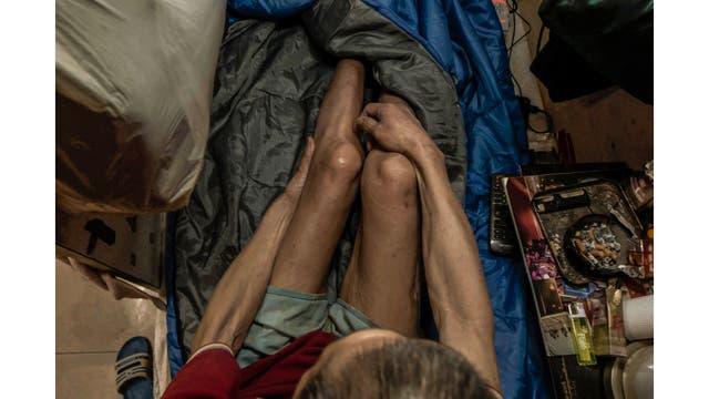 Wong Tat-ming, de 63 años, se sienta rodeado de sus escasas posesiones