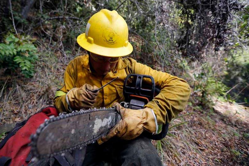 Un brigadista repara la sierra con la deberá seguir trabajando en las zonas afectadas. Foto: LA NACION / Emiliano Lasalvia
