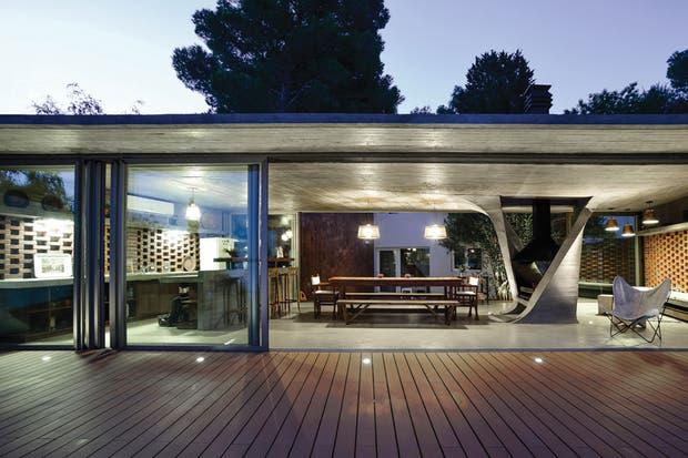 El espacio tiene un sector de cocina con barra y banquetas 'Bar'; una zona de comedor con lámparas 'Maderitas', mesa y banco modelo 'V' y a continuación, el área de estar con un trío de lámparas 'Otto' de cobre, tacos de madera 'Álamo' (todo de Net Muebles) y un emblemático sillón 'BKF'.  /Mike Mercau
