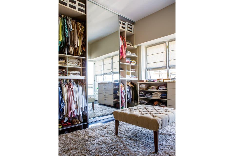 El espacio del vestidor tiene un mueble perimetral en melamina con puertas corredizas de frente espejado. Complementa una banqueta capitoné tapizada en arpillera y botones forrados sobre la alfombra de pelo beige.  Foto:Living /Santiago Ciuffo
