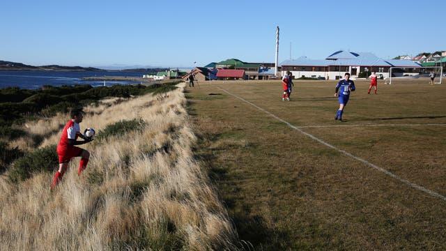 Varias veces durante el partido, los jugadores tuvieron que buscar la pelota en los pastizales que bordean la cancha de fútbol de Puerto Argentino. Foto: LA NACION / Mauro V. Rizzi