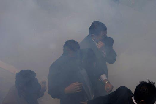 El presidente de Ecuador, Rafael Correa; quedó atrapado en medio de una ola de gases lacrimógenos durante a protesta de policías y soldados por el recorte presupuestario. Foto: AP