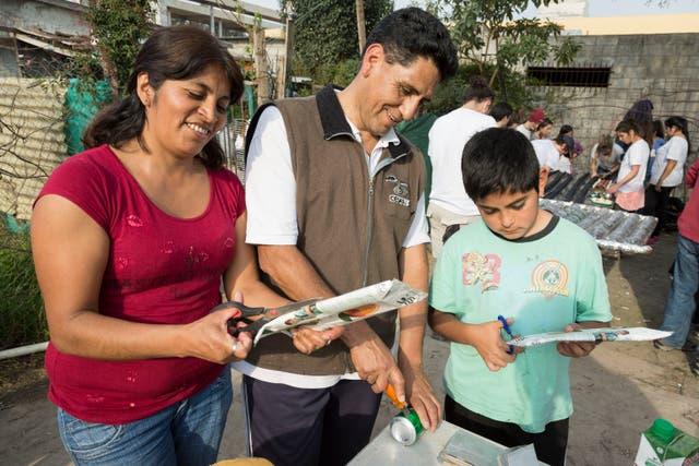 Ofelia y César Flores, junto a una de sus hijos, colaboran en la construcción del calefón