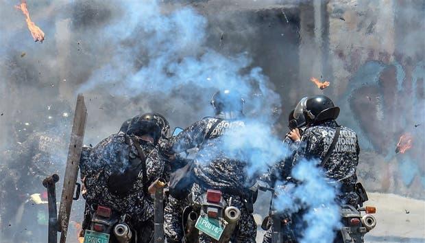 Un grupo de policías se cubre tras la explosión de un artefacto casero en Altamira, Caracas