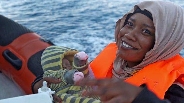 Un inmigrante somalí lleva a su bebé de 12 días a bordo de la ONG Migrant Offshore Aid Station (MOAS) de Malta durante una operación de rescate de un barco de madera en el mediterráneo en aguas internacionales de la costa de Sabratha en Libia