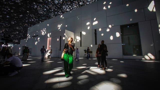 Una persona camina bajo las luces que atraviesan la cúpula del Louvre Abu Dhabi