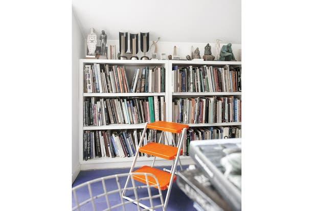 La biblioteca con sus libros y un póster enmarcado de Alfred Hitchcock, una caricatura de Al Hirschfeld comprada en el primer viaje que hicieron a Nueva York. La escalerilla naranja es de la firma italiana Magis ($2.190, Arquimadera)..