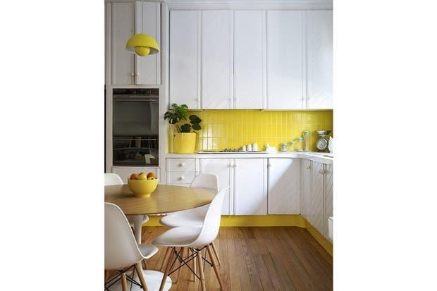El amarillo de los cerámicos juega con los zócalos coloreados en el mismo tono. Foto: www.designsponge.com.