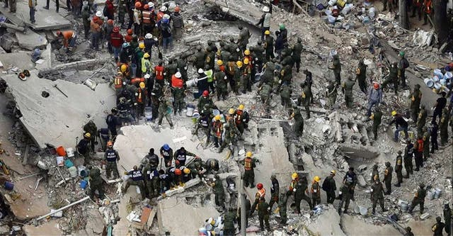 Rescatistas, bomberos, policías y civiles buscan sobrevivientes en los escombros de un edificio, en Ciudad de México