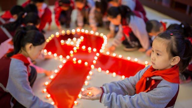 Un grupo de niños prende velas en un homenaje en una escuela primaria