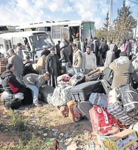 Un grupo de egipcios ordena sus pertenencias para ingresar en Túnez desde Ras Ajdir