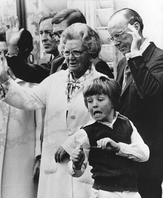Travesuras de niños: esta imagen es de 1978. Friso improvisa una honda mientras sus abuelos, la reina Juliana y el príncipe Bernhard, saludan a la gente. Foto: /AP y Getty Images