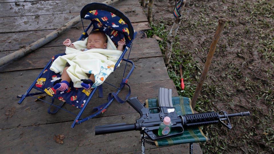 Alexis Patino de 3 meses de edad duerme junto al arma de su madre, Deisy García. Foto: AP / Fernando Vergara