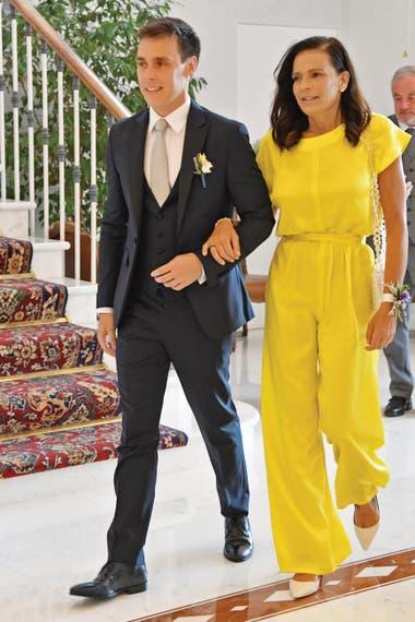 La princesa del brazo de su hijo. Estefanía vestida con un mono color amarillo intenso y una pulsera floral, un guiño al diseño y al ramo de la novia.
