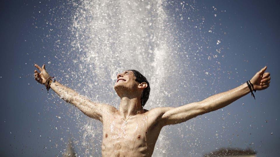 La gente en las calles se refresca con el agua de las fuentes . Foto: AFP