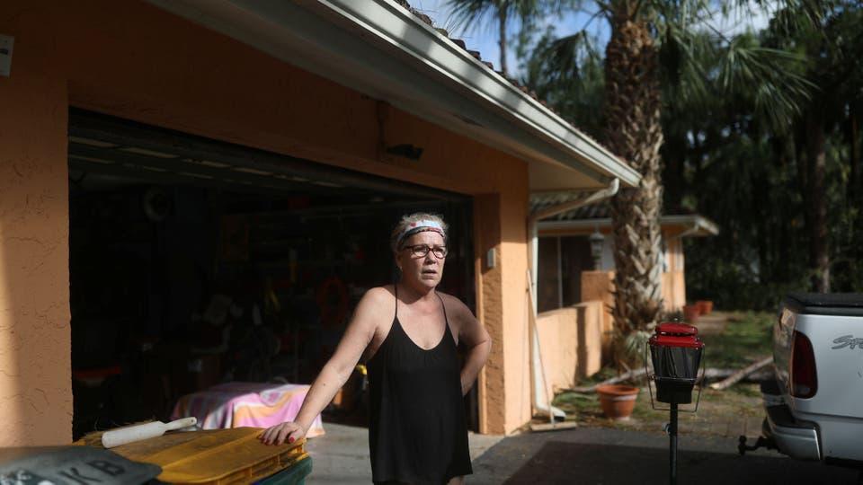 Linda Benson en la puerta de su casa intenta rescatar lo que pueda de sus pertenencias. Foto: Reuters