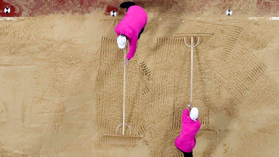 Clasificación para el salto de longitud femenino Los trabajadores preparan la arena.. Foto: Reuters