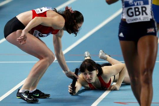Así es difícil ganar... la búlgara Khiustava pasa el testimonio desde el piso. Foto: AFP / AP, Reuters y EFE
