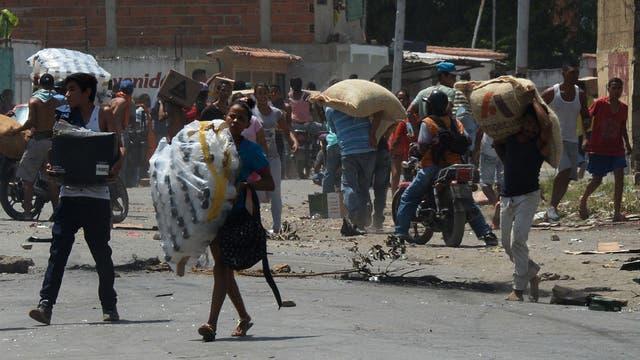 La gente lleva la mercancía durante saqueos en Maracay, estado de Aragua.