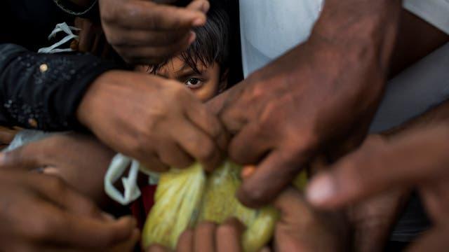 Refugiados de la minorías étnicas de Rohingya recién llegados de Myanmar buscan raciones de comida cerca del campo de refugiados de Kutupalong en Ukhia, Bangladesh