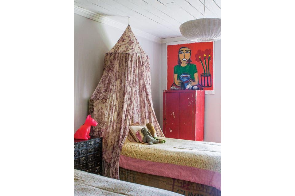 En el cuarto de Francesca, juego de camas forradas en arpillera con baldaquino y acolchados (Paula Cahen D'Anvers), ropero rojo de ferrocarril y cajonera que hace de mesa de luz. La luz de noche es un perrito fucsia (Jonathan Adler).  Foto:Living /Santiago Ciuffo
