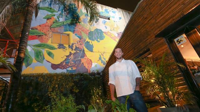 Alejandro Feraud en la entrada de su restaurant junto al mural de Bernardo Ezcurra.