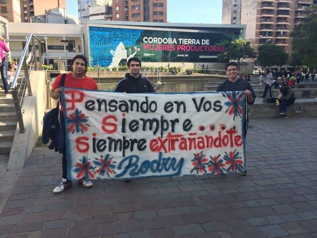 """Sus amigos llevan una bandera con la frase """"Pensando en vos siempre, siempre extrañandote"""" a cada lado que van"""