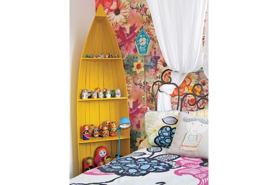La habitación de Manu tiene un sector de estar con una biblioteca pintada en azul Tiffany, elegido por la dueña del cuarto, y un sofá con almohadones 'Uglydoll'. El contexto de la cama remite a una auténtica casa de muñecas con empapelado de Farm (la marca de su mamá) y acolchado también con flores .  /André Luiz Cronemberger Nazareth