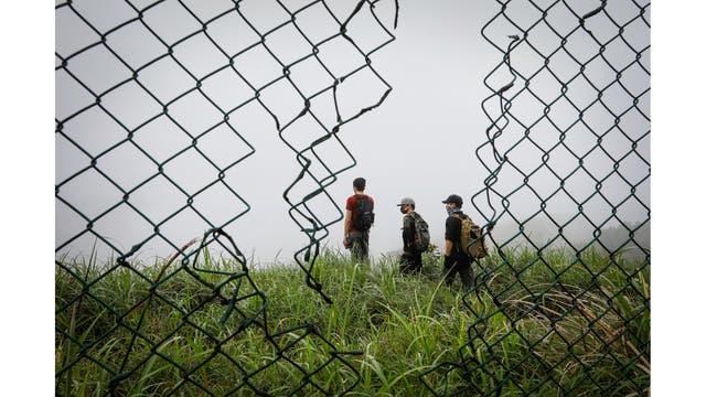 Activistas de HK URBEX a través de un agujero de un alambrado