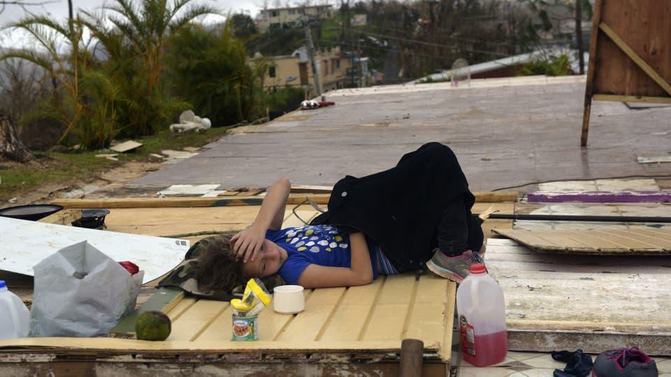 Una niña descansa sobre los restos de su casa. Foto: DPA/ Carol Guzy