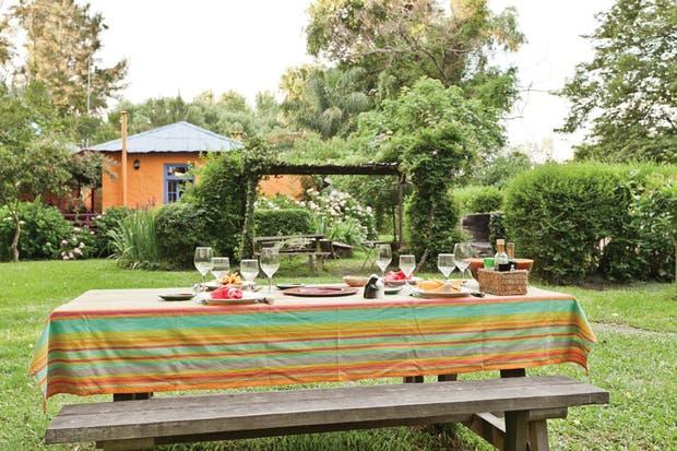 Detrás de la mesa del jardín se hizo una pérgola en la que hay una parrilla y un horno de barro..