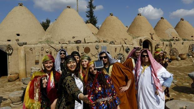 Un autorretrato grupal de turistas vestidos con trajes típicos en Harran, Turquía