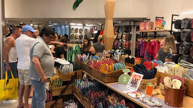 Turistas comprando en un conocido local de ojotas y ropa de playa