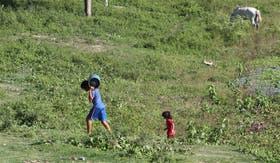 Un chico carga al hombro una garrafa de gas, vadeano el Pilcomayo, mientras su pequeña hermanita lo sigue, en uno de los pasos ilegales entre Paraguay y Formos