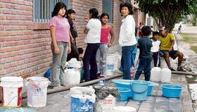 La gente espera que los camiones y los carros aguateros llenen sus recipientes y baldes de agua potable