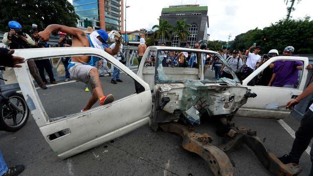 La oposición desmantela un auto viejo para hacer barricadas. Foto: AFP / Federico Parra