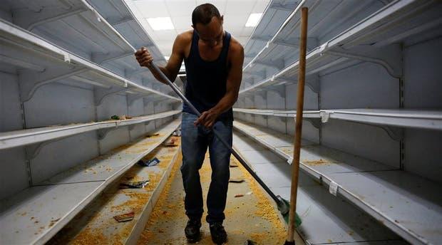 Un empleado limpia las góndolas de un supermercado de Caracas tras un saqueo