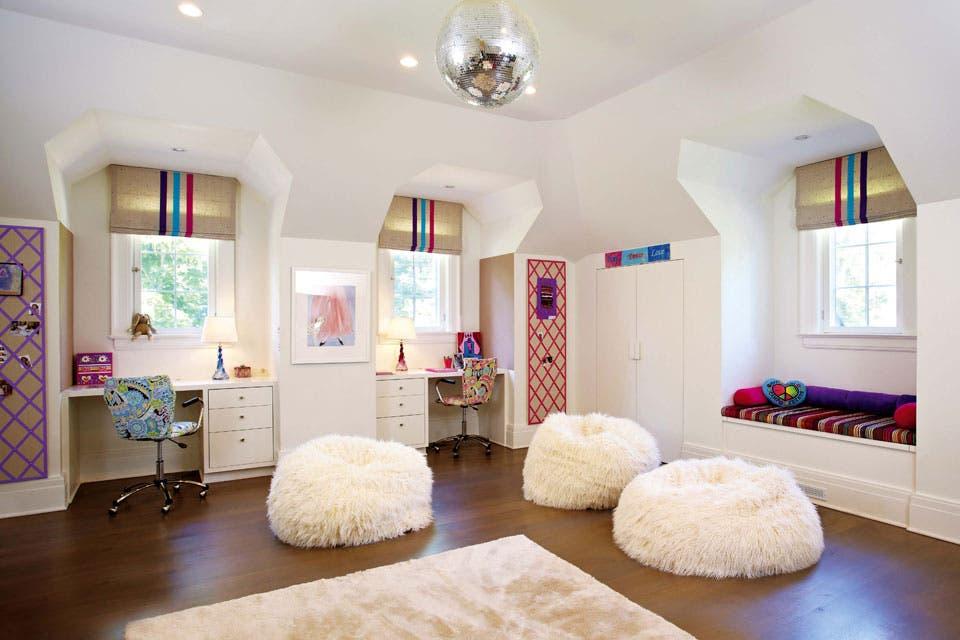 Una alfombra (Stark), grandes pufs blancos (Pottery Barn) y una bola de espejos delimitan el sector de juego.  Foto:Living /Rachel Laxer Interiors