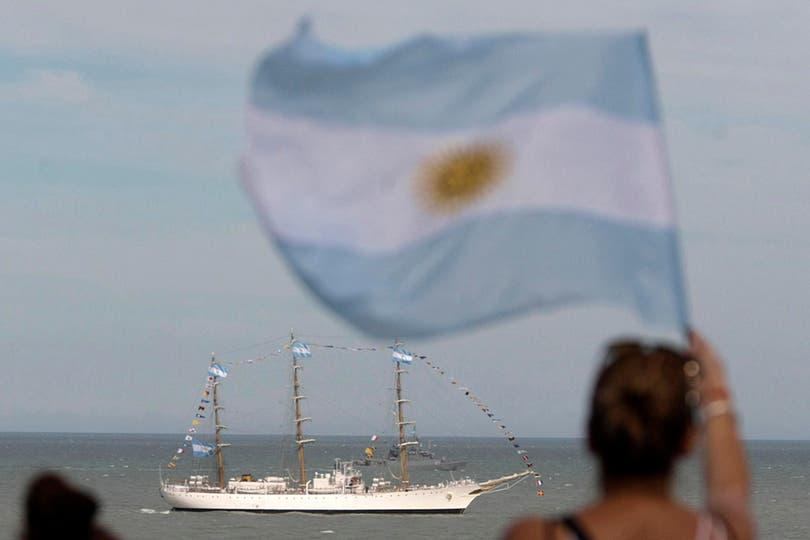 Una mujer desde la costa saluda a la Fragata con una bandera argentina. Foto: LA NACION / Mauro V. Rizzi