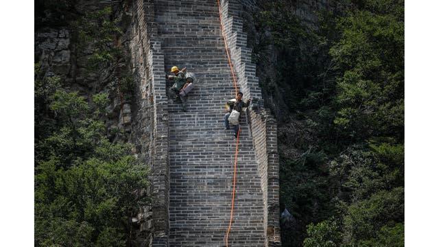 Obreros bajan por la sección Jiankou de la Gran Muralla llevando sus herramientas y pertenencias