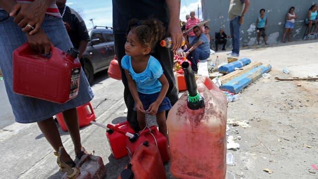 Una niña y su madre hacen cola para conseguir agua . Foto: AP / Gerald Herbert