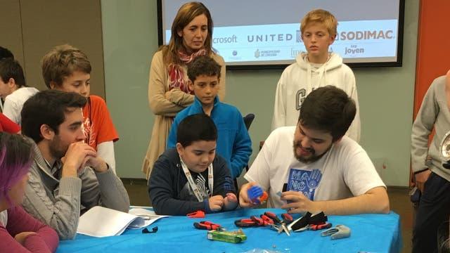 Gino Tubaro ayuda en el ensamblado de una prótesis; de pie, con remera roja, está David, otro de los 20 chicos que se llevaron una mano hecha con una impresora 3D