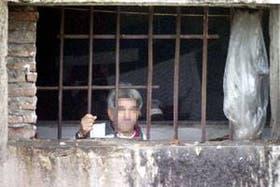 Un recluso mira a través de una ventana sin vidrios en un pabellón de Olmos