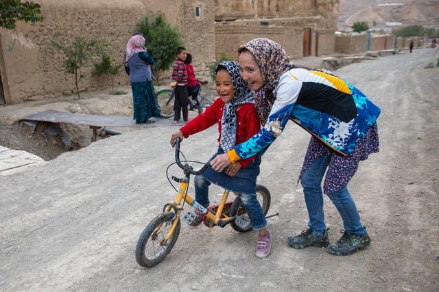 Zakia Mohammadi le enseña a una niña afgana a andar en bicicleta