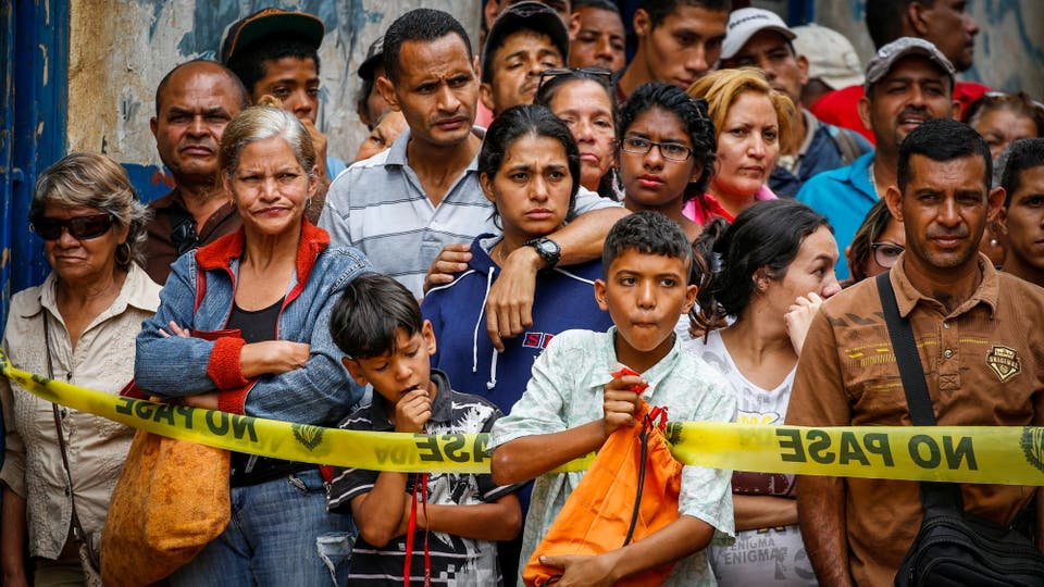 La gente mira el operativo policial que tiene lugar en las afueras de una panaderia. Foto: Reuters / Carlos Garcia Rawlins