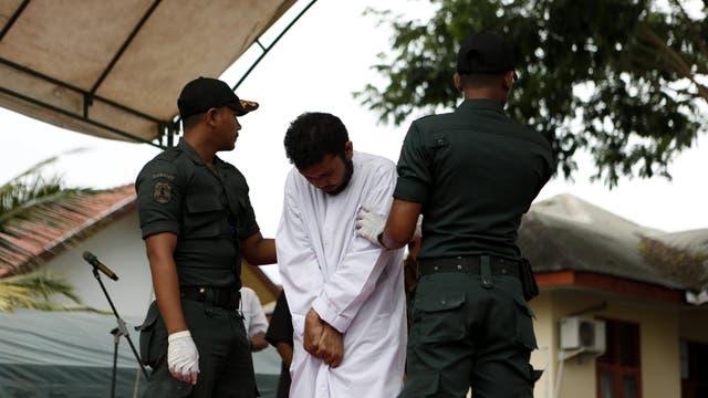 Un hombre es escoltado antes de recibir 83 azotes públicos en Aceh, la única provincia de Indonesia donde se aplica la sharia (ley islámica).