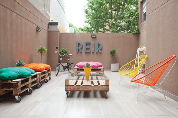 El patio se transformó en un gran living gracias al sencillo equipamiento que el dueño de casa construyó con sus propias manos: un par de sillones con almohadones en forma de nube ($650, Nippon Deco), dos mesas realizadas con pallets y prácticas ruedas.  /Javier Picerno