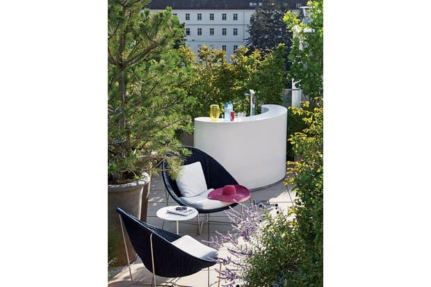 El departamento está prácticamente rodeado por una terraza. Semioculto en el rincón más verde, un bar para disfrutar del buen clima apoltronado en sillas 'Nido (Paola Lenti).  Foto:Living /Francis Amiand / Kerylos Intérieurs