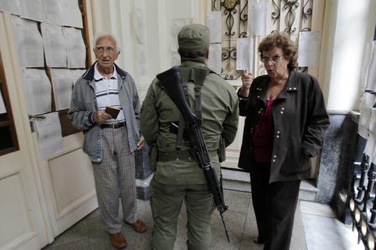 Una paareja se busca en los padrones con la ayuda de un soldado del ejécito argentino. Foto: EFE