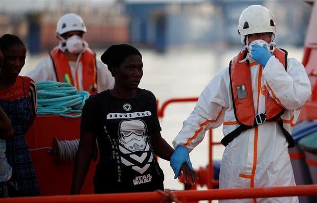Un migrante es ayudado a descender de un barco humanitario en el Málaga